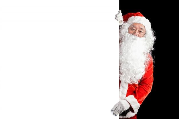 Szczęśliwy święty mikołaj mienia reklamy sztandaru pusty tło z kopii przestrzenią. uśmiechający się święty mikołaj wskazuje w białym puste miejsce znaku. motyw świąteczny, sprzedaż