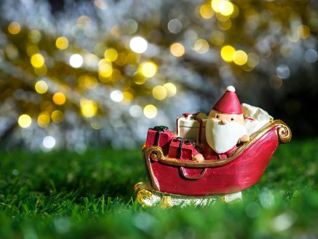 Szczęśliwy święty mikołaj z pudełkiem prezentów na saniach śniegowych w tle jest świąteczny wystrój.