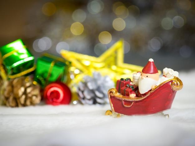 Szczęśliwy święty mikołaj z pudełkiem prezentów na sankach jest świąteczny wystrój.