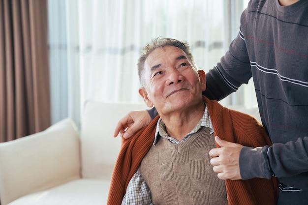 Szczęśliwy syn zakrywający ojca kocem w ich domu. starszy mężczyzna i szczęśliwa rodzina.