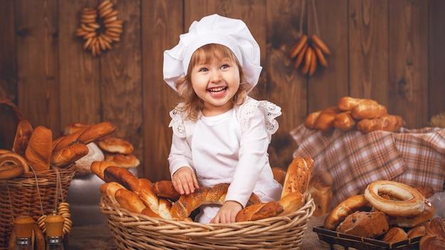 Szczęśliwy szef kuchni dziecka w wiklinowym koszu śmiejąc się