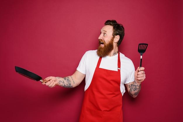 Szczęśliwy szef kuchni gotuje nowy kreatywny przepis na czerwono