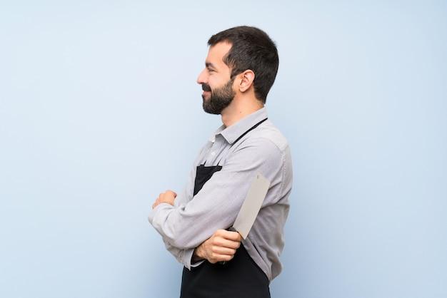 Szczęśliwy szef kuchni na niebieską ścianą
