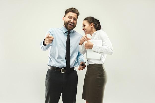 Szczęśliwy szefie. mężczyzna i jego sekretarz stojący w biurze