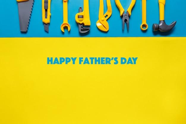 Szczęśliwy tag dzień ojca z narzędziami zabawki na niebieskim żółtym tle widok z góry z miejsca kopiowania tekstu.