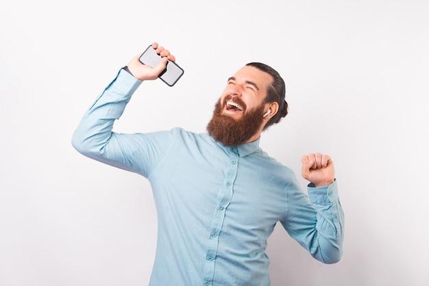 Szczęśliwy tańczący mężczyzna cieszy się muzyką, której słucha przez słuchawki i telefon