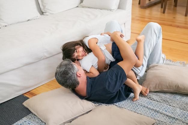 Szczęśliwy tata bawi się z wesołym małym synkiem i córką.