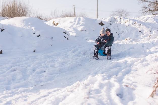 Szczęśliwy tata i mały chłopiec bawi się saniami śnieżnymi