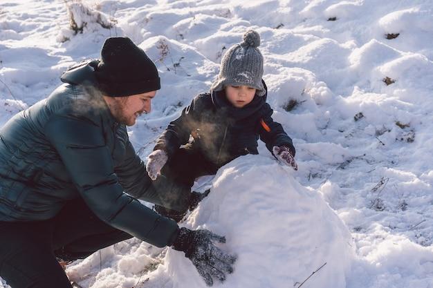 Szczęśliwy tata i mały chłopiec bawi się śniegiem