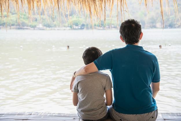 Szczęśliwy tata i syn podczas wakacje przy wodnej strony naturą