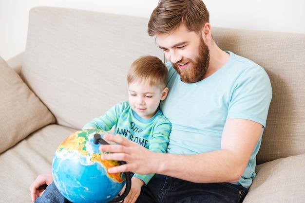 Szczęśliwy tata i syn siedzą i patrzą na kulę ziemską razem w domu
