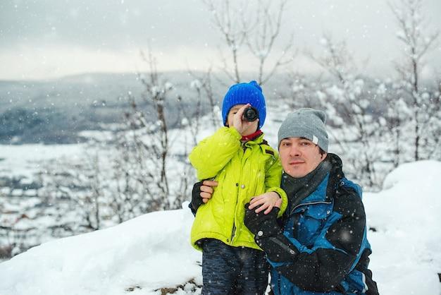 Szczęśliwy tata i syn w zimowym lesie