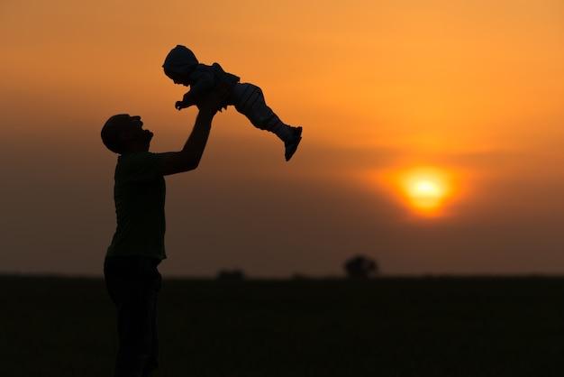 Szczęśliwy tata rzuca dziecko o zachodzie słońca