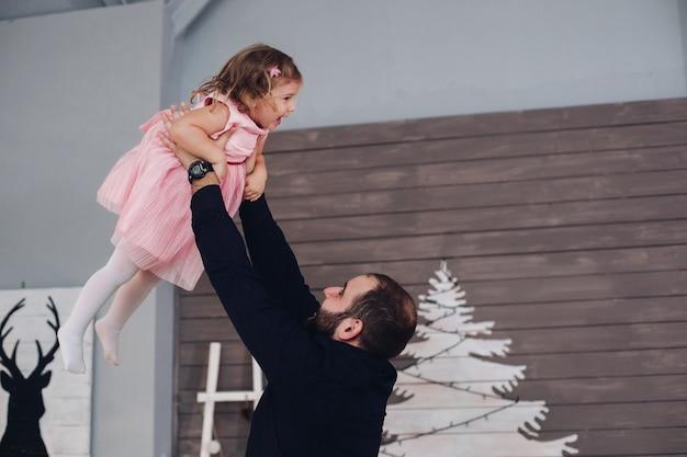 Szczęśliwy tata trzyma córkę w ramionach i wiruje z nią