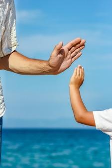 Szczęśliwy tata trzyma rękę dziecka nad greckim morzem w naturze