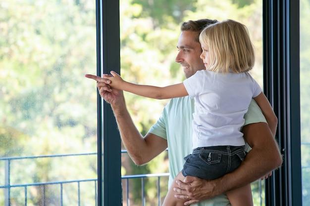 Szczęśliwy tata trzyma śliczną córkę i wskazuje gdzieś