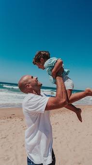 Szczęśliwy tata z synem malucha, grając na piaszczystej plaży nad oceanem
