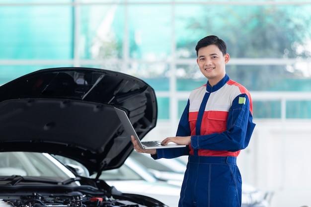 Szczęśliwy technik lub mechanik samochodowy sprawdzanie systemu silnika nowego samochodu z komputerem przenośnym w centrum obsługi samochodów.