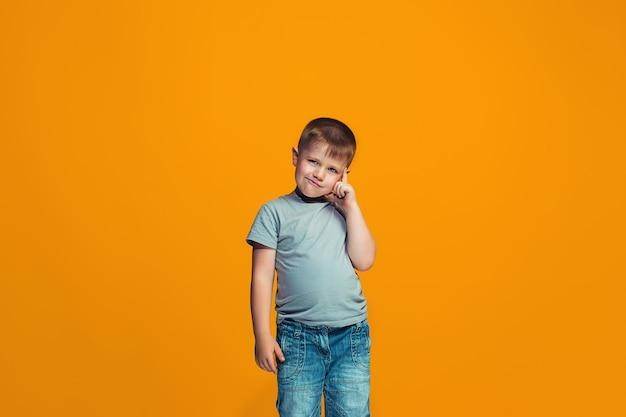 Szczęśliwy teen chłopiec stoi i uśmiecha się przeciwko przestrzeni pomarańczowej.