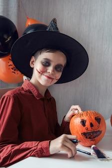 Szczęśliwy teen chłopiec w kostiumie przygotowuje się do obchodów halloween rysowanie dyni