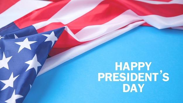 Szczęśliwy tekst dnia prezydentów na niebieskim tle z flagą narodową stanów zjednoczonych