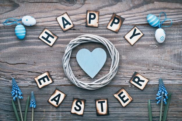 Szczęśliwy tekst wielkanocny na rustykalnym drewnie z niebieskim sercem w wieniec, kwiaty i pisanki