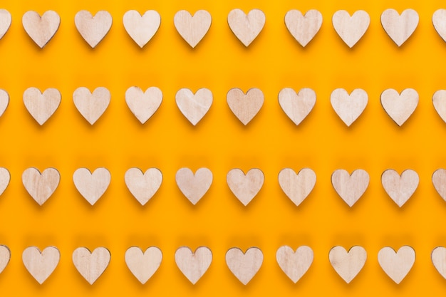 Szczęśliwy tło walentynki. z małymi kolorowymi serduszkami na żółtym tle.