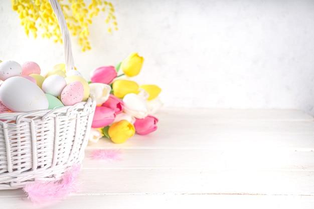 Szczęśliwy tło wielkanoc z kolorowych jaj w koszyku i wiosennych kwiatów. wielkanocna wiosna holidat powitanie karta tło