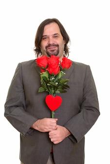 Szczęśliwy tłuszczu biznesmen kaukaski uśmiechnięty gospodarstwa czerwone róże i serce gotowe na walentynki