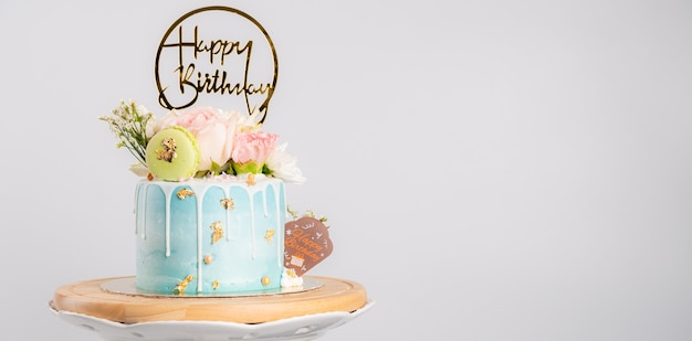 Szczęśliwy tort urodzinowy z makaronikami i kwiatami na stojaku
