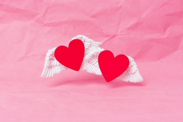 Szczęśliwy transparent walentynki. czerwone drewniane serce z białymi obszernymi skrzydłami szybuje na różowym zmiętym tle papieru. minimalizm. miejsce na tekst