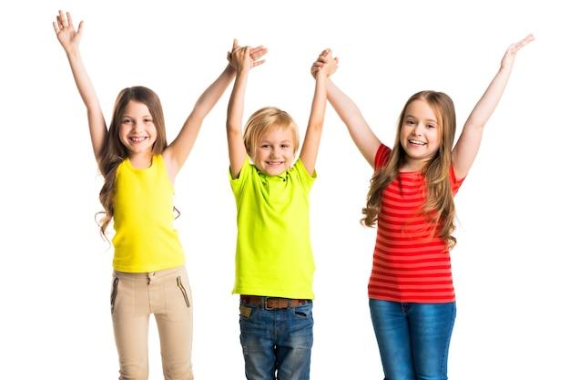 Szczęśliwy troje dzieci trzymając podniesione ręce na białym tle na białej powierzchni