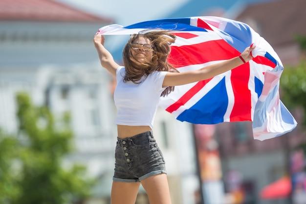 Szczęśliwy turysta dziewczyna spaceru na ulicy z flagą wielkiej brytanii.