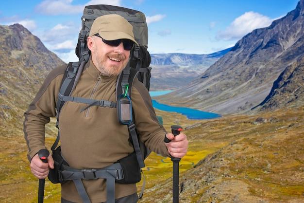 Szczęśliwy turysta mężczyzna z plecakiem podróżuje po górach