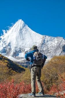 Szczęśliwy turysta na szczycie góry z plecakiem