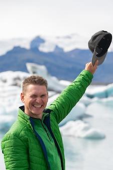 Szczęśliwy turysta patrząc na widok krajobraz gór lodowych z gigantycznymi górami lodowymi i jeziorem