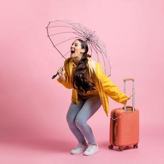 Szczęśliwy turysta trzyma jej bagaż podczas gdy patrzejący daleko od