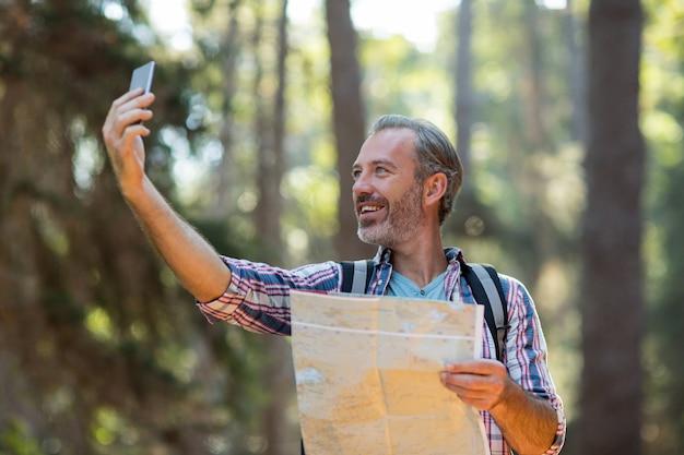 Szczęśliwy turysta z mapą przy selfie