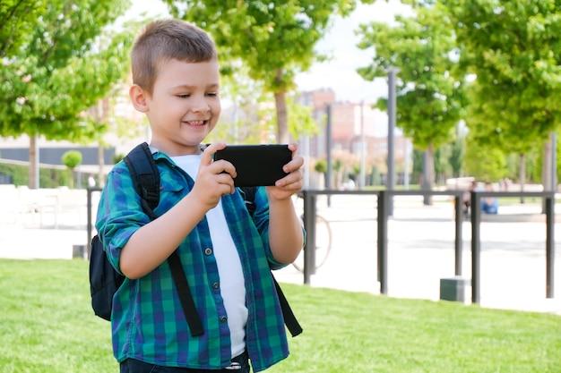 Szczęśliwy uczeń patrzący na ekran smartfona i uśmiechnięty, rozmowa wideo, gry online na smartfonie
