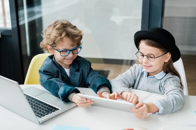 Szczęśliwy uczeń podstawowa, wskazując na ekranie touchpada podczas prezentacji koledze z klasy przy biurku