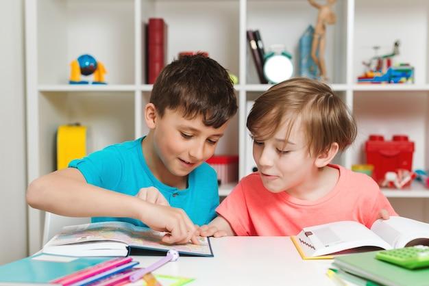 Szczęśliwy uczeń robi test w szkole podstawowej. dzieci piszące notatki w klasie. chłopcy w szkole razem odrabiają lekcje.