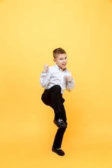 Szczęśliwy uczeń skacze z radości. pojedynczo na żółtej powierzchni. koncepcja szczęścia, aktywności i dziecka.