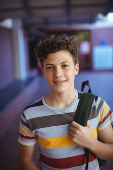 Szczęśliwy uczeń stojący w kampusie szkolnym