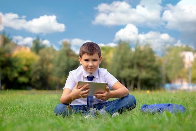 Szczęśliwy uczeń w białej koszuli i niebieskim krawacie siedzi na zielonej trawie na tle błękitnego nieba z białymi chmurami i trzyma tablet.