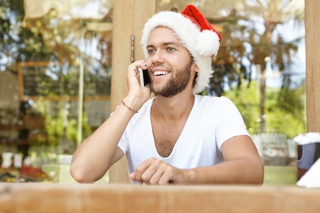 Szczęśliwy uczeń w kapeluszu świętego mikołaja rozmawia przez telefon komórkowy