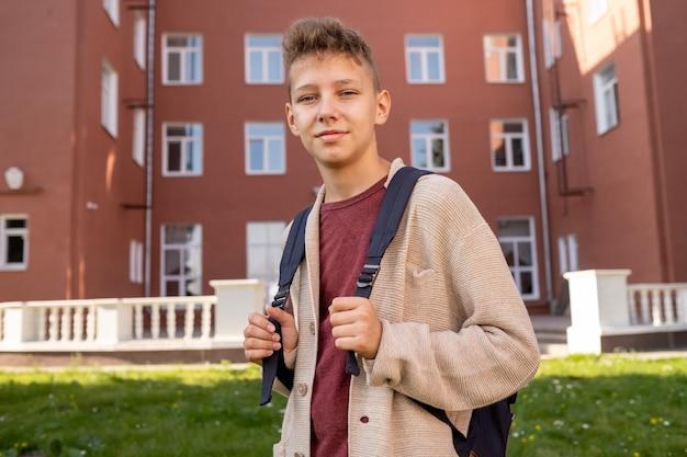 Szczęśliwy uczeń z plecakiem stojący na zielonym trawniku przed szkołą