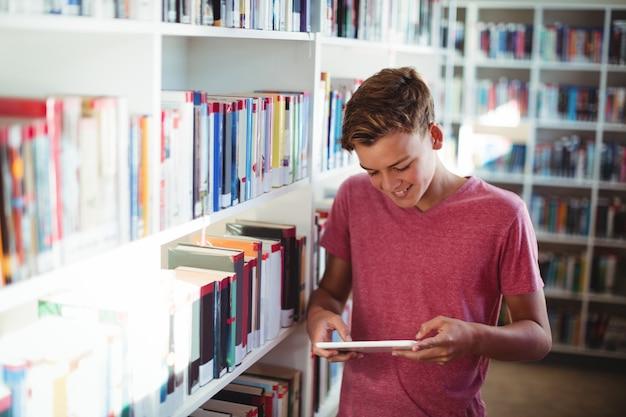 Szczęśliwy uczeń za pomocą cyfrowego tabletu w bibliotece