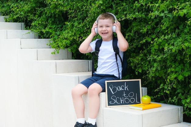 Szczęśliwy uczniak w słuchawkach trzymający znak