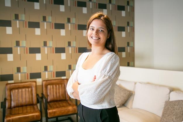 Szczęśliwy udany młody biznes kobieta stoi z założonymi rękoma i pozowanie we wnętrzu coworking lub kawiarnia, patrząc na kamery i uśmiechnięty