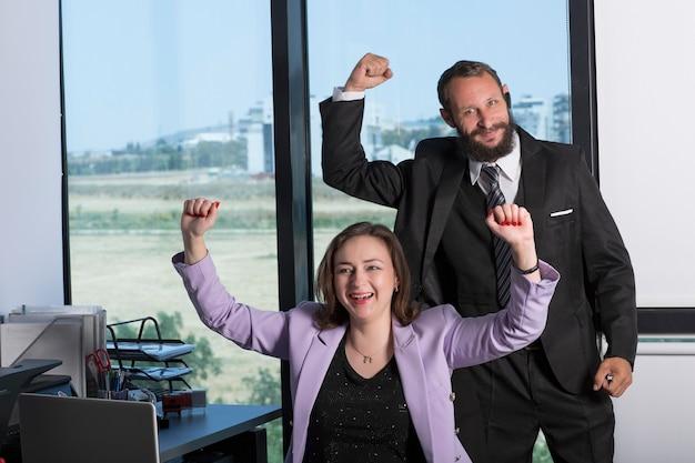 Szczęśliwy udany uśmiechający się biznes kobieta podniosła ręce do góry, siedząc przy stole w biurze. współpracownicy united podnoszą ręce, by uczcić swoje osiągnięcie. koncepcja sukcesu i pracy zespołowej